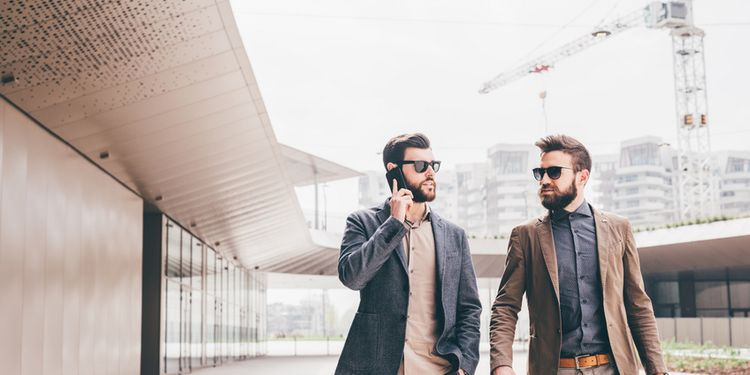 two contemporary businessman walking talking smart phone